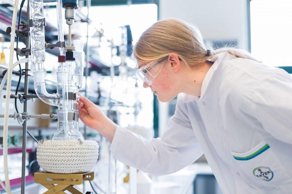 Eine Frau beobachtet in Schutzkleidung einen chemischen Aufbau im Labor.