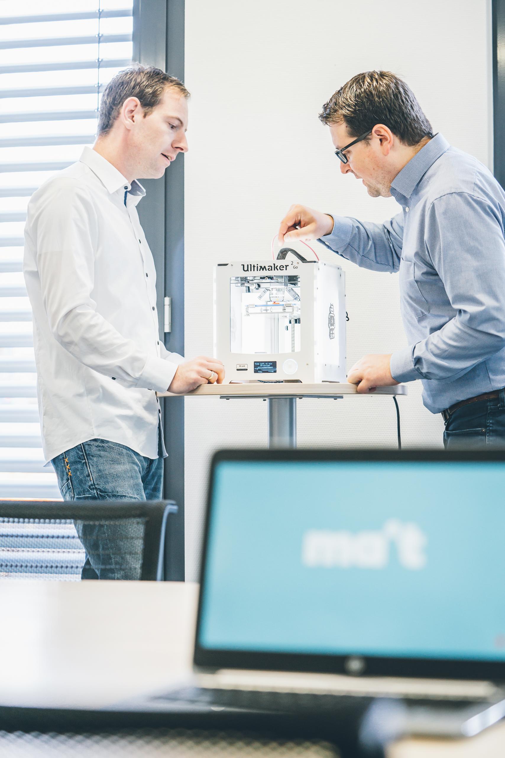 Zwei Männer im Büro schauen sich eine kleine Maschine an