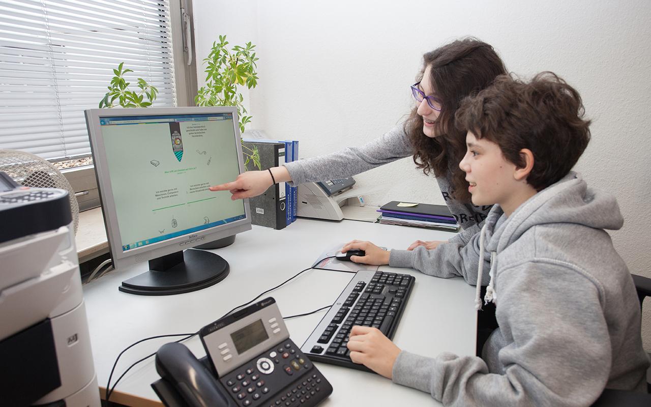 Jugendliche schauen auf einen Rechner