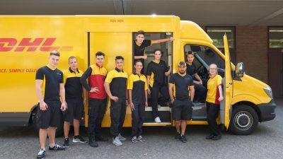 10 Jugendliche stehen vor einem DHL Transporter