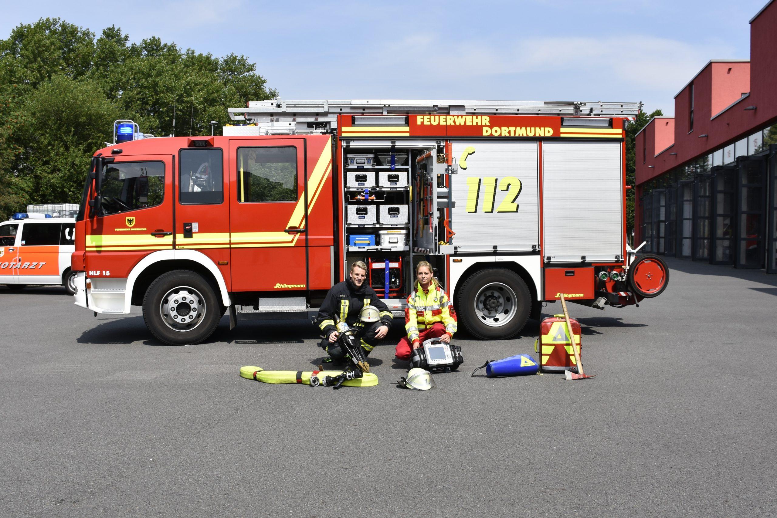 Menschen vor einem Feuerwehr-Wagen